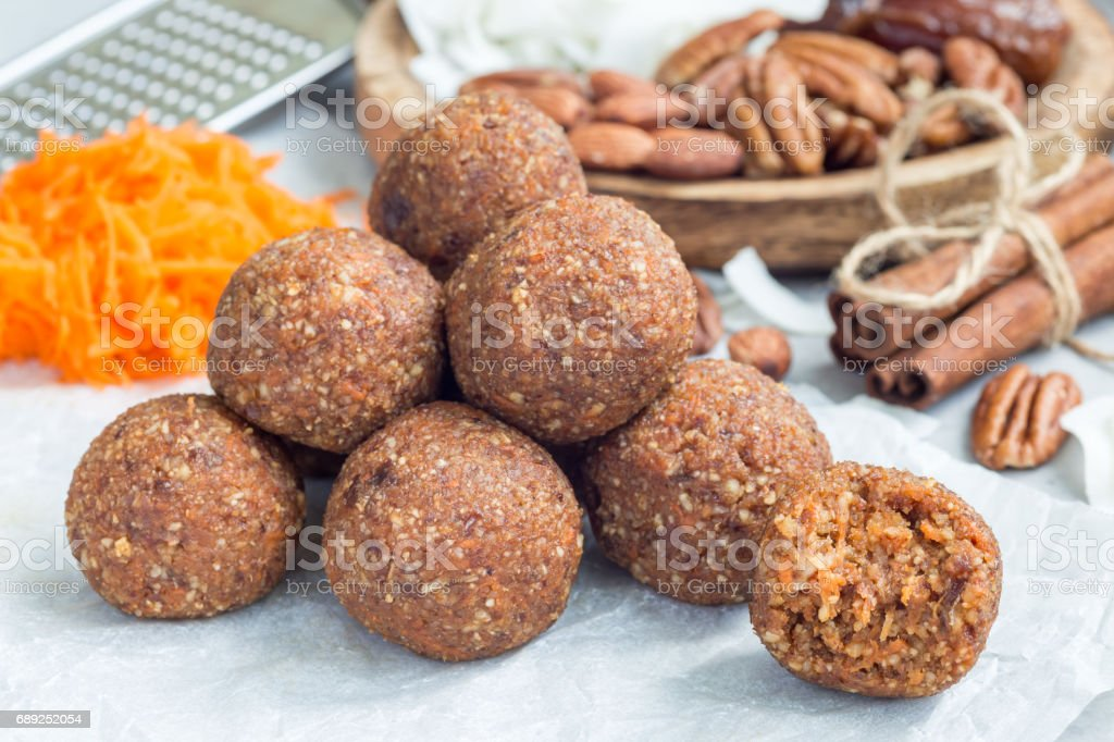 Healthy homemade paleo energy balls with carrot, nuts, dates and coconut flakes, on parchment, horizontal stock photo