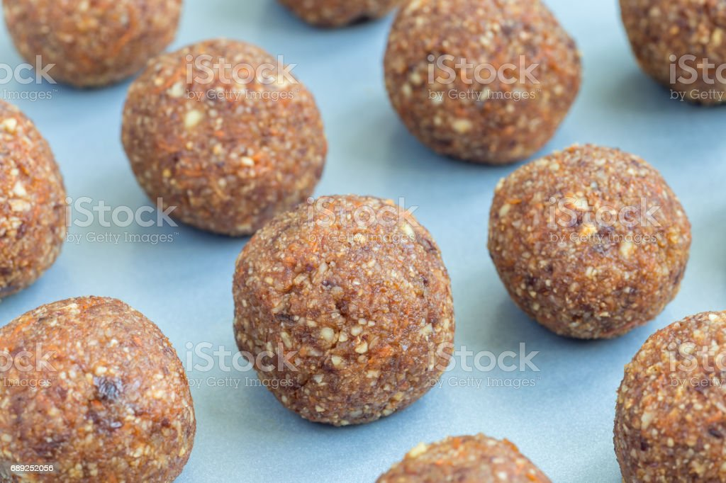 Healthy homemade paleo energy balls with carrot, nuts, dates and coconut flakes, on tray, horizontal stock photo
