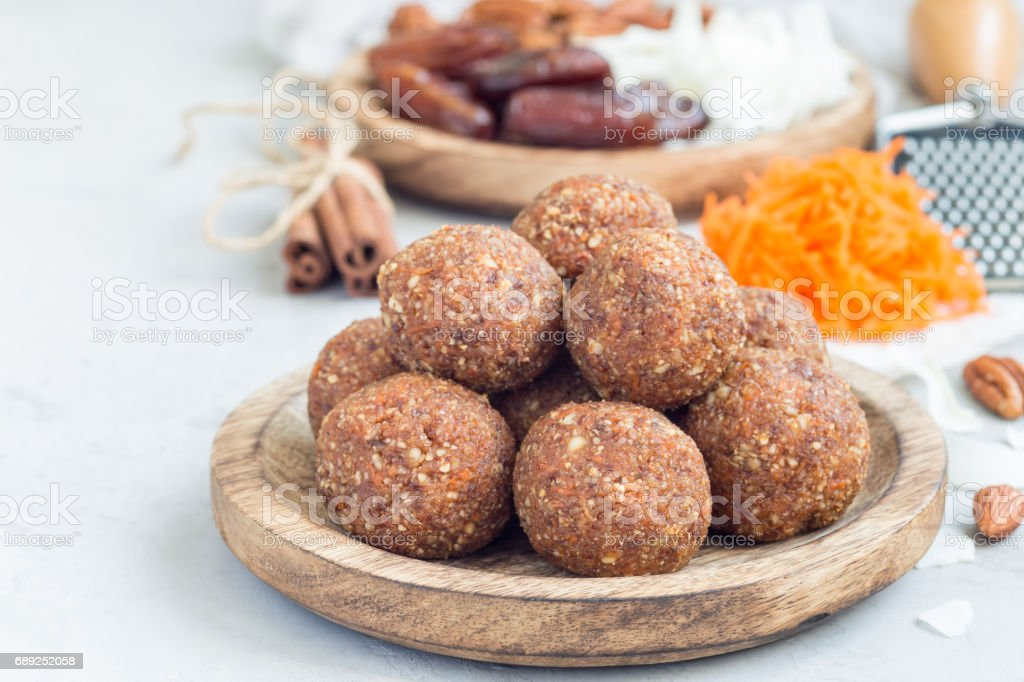 Healthy homemade paleo energy balls with carrot, nuts, dates and coconut flakes, on wooden plate, horizontal, copy space stock photo
