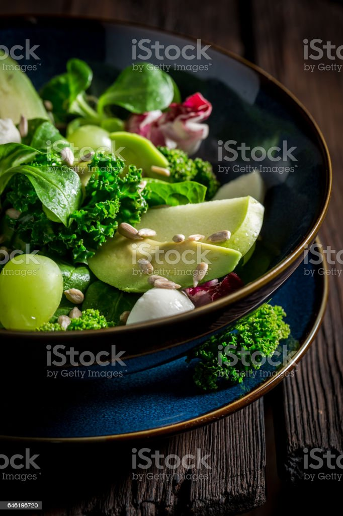 Healthy kale salad with mix of vegetables and avocado stock photo