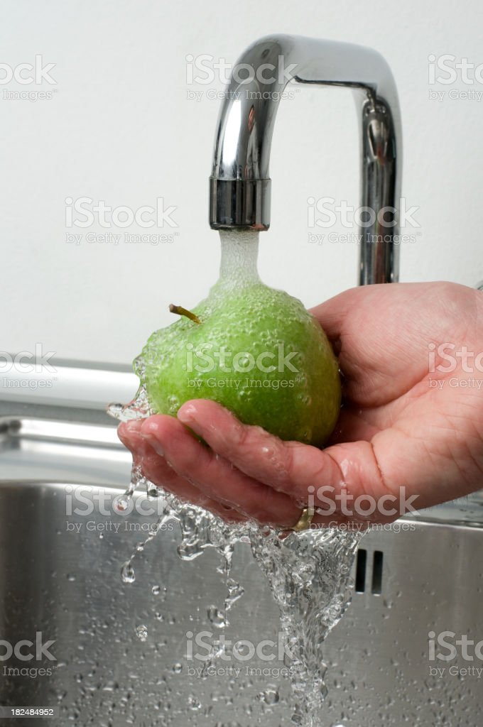 Healthy Lifestyle as hand holds green apple under running water royalty-free stock photo