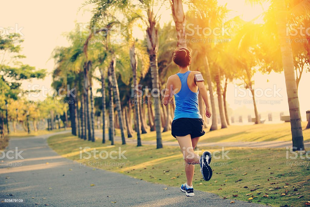 healthy lifestyle asian woman jogging at tropical park stock photo