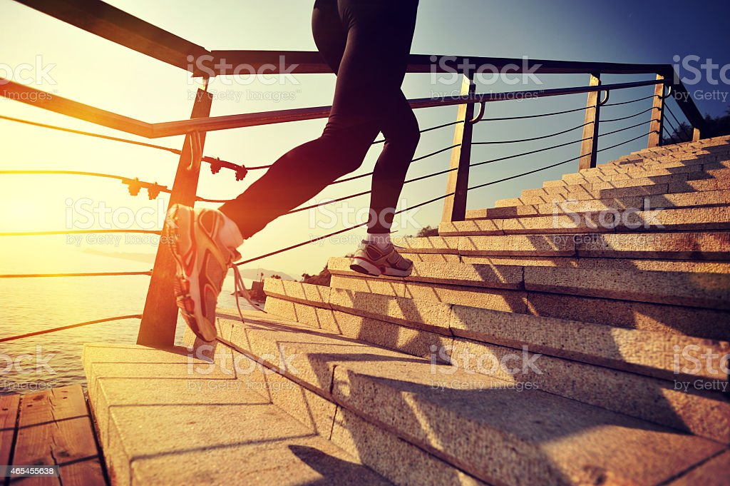 healthy lifestyle asian woman running at stairs seaside stock photo