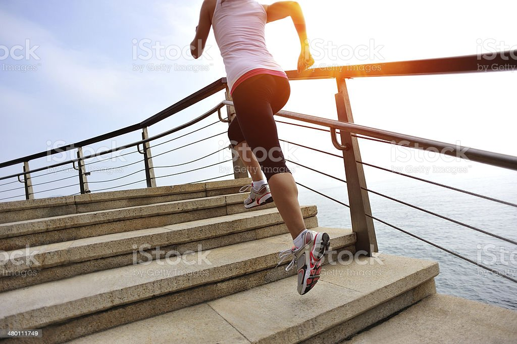 healthy lifestyle asian woman running at stone stairs seaside stock photo