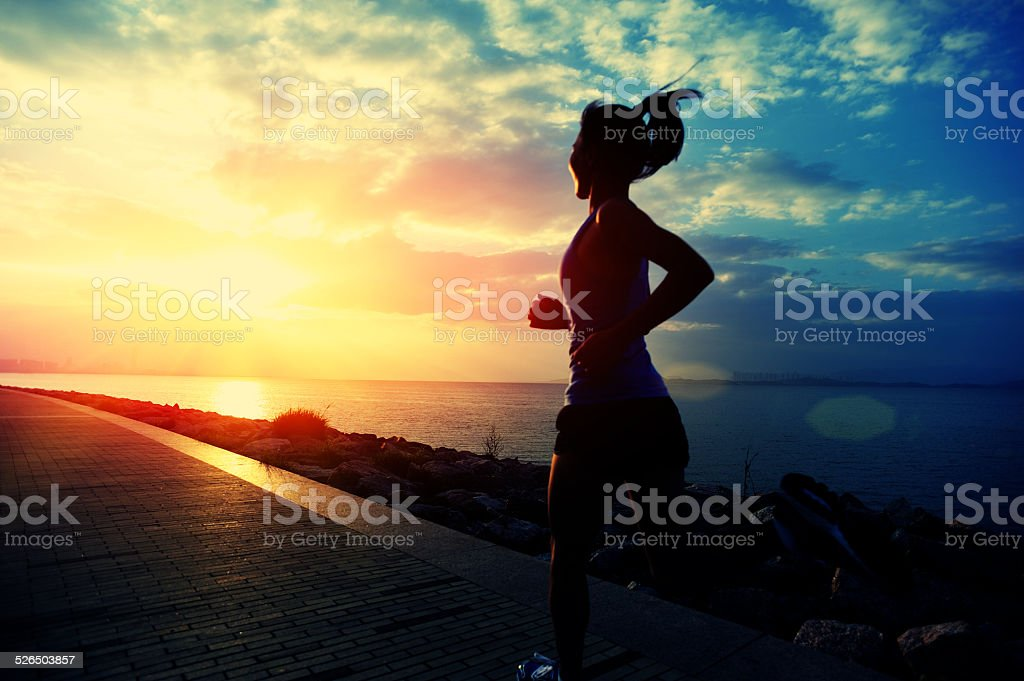 healthy lifestyle asian woman running at sunrise seaside stock photo