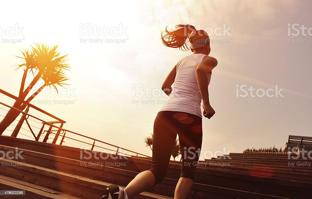 healthy lifestyle asian woman running up at wooden stairs royalty-free stock photo