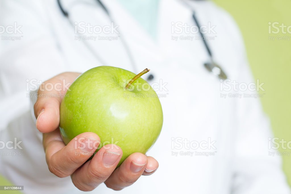 Healthy lifestyle diet abstract concept with doctor and green apple stock photo