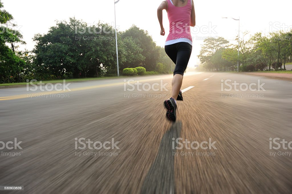 healthy lifestyle fitness sports woman running on road stock photo