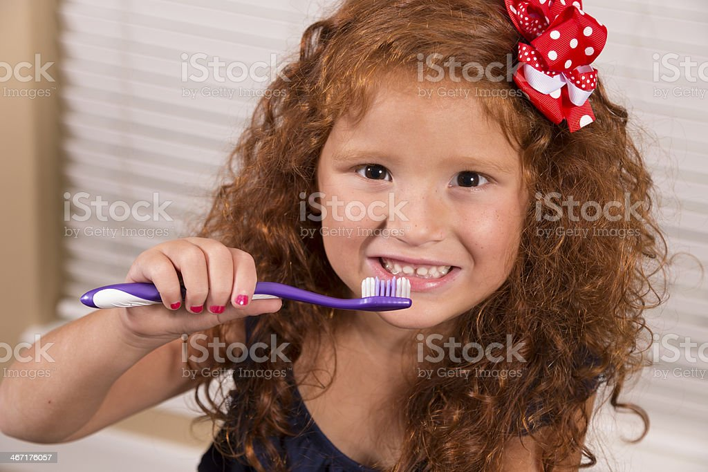 Healthy Lifestyle:  Happy young red-haired girl brushing her teeth. royalty-free stock photo