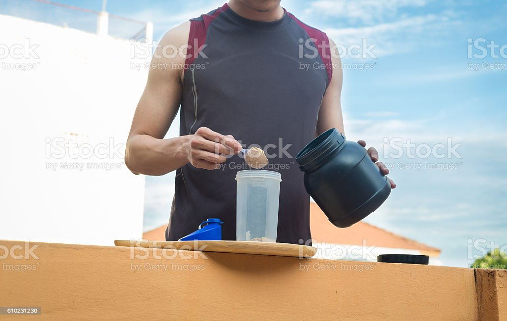Healthy lifestyle, man pour whey powder on the bottle. stock photo