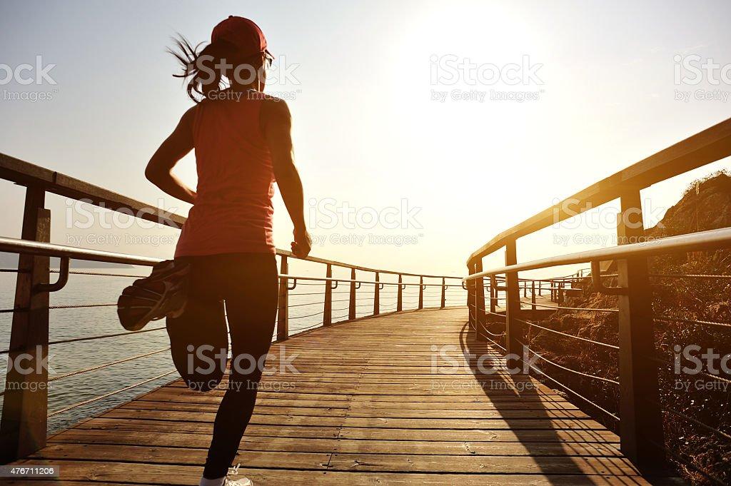 healthy lifestyle sports woman running on wooden boardwalk sunrise seaside stock photo