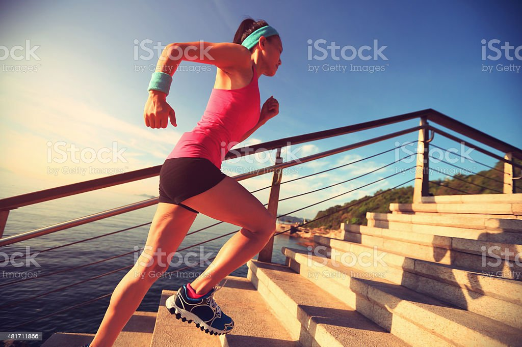 healthy lifestyle sports woman running up on stone stairs seaside stock photo