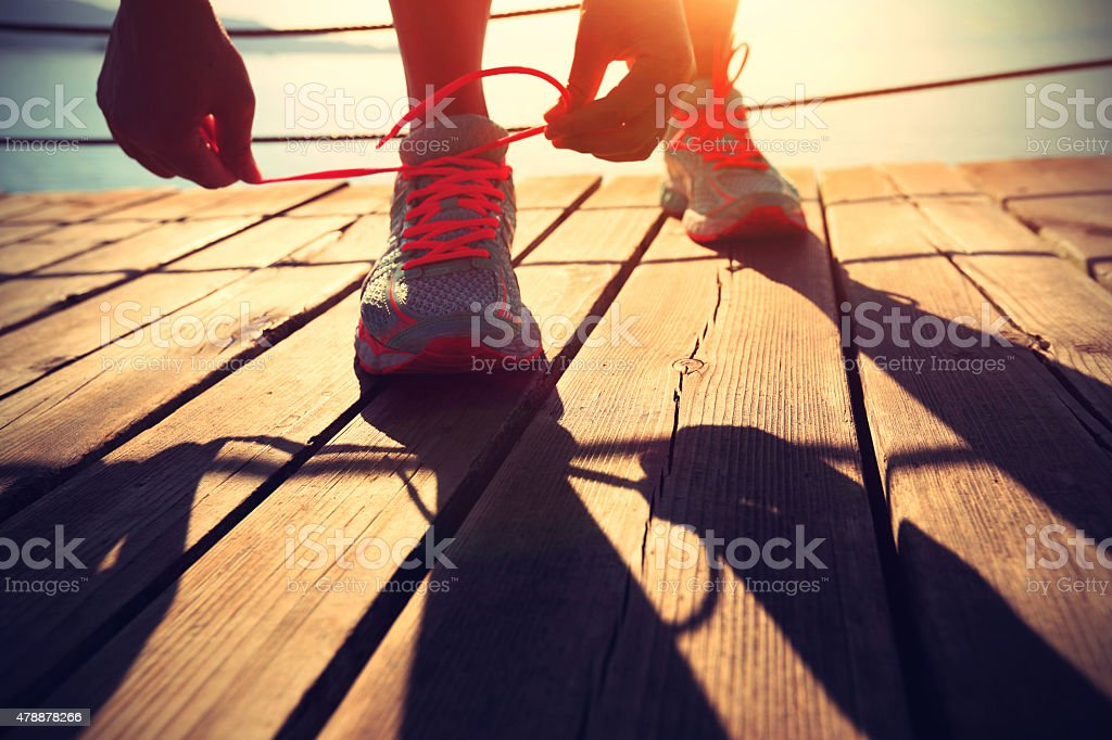 healthy lifestyle sports woman tying shoelace stock photo