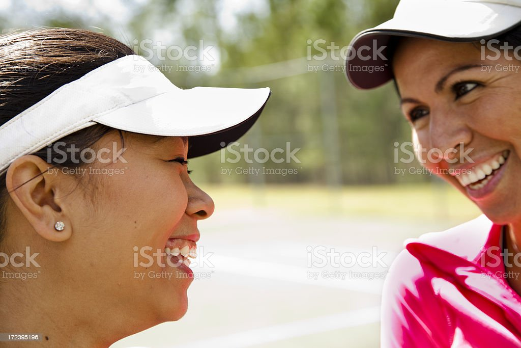 Healthy Lifestyle:  Two ladies laughing on the tennis court royalty-free stock photo