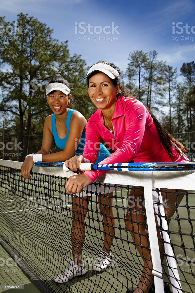 Healthy Lifestyle:  Two smiling ladies leaning over tennis net royalty-free stock photo