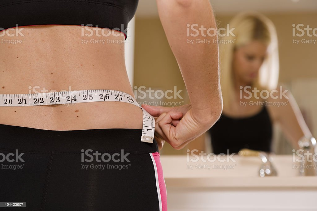 Healthy Lifestyle:  Weight conscious woman measuring her waist. Mirror reflection. royalty-free stock photo