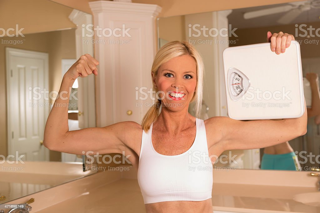 Healthy Lifestyle:  Weight conscious woman shows muscles and scale. royalty-free stock photo
