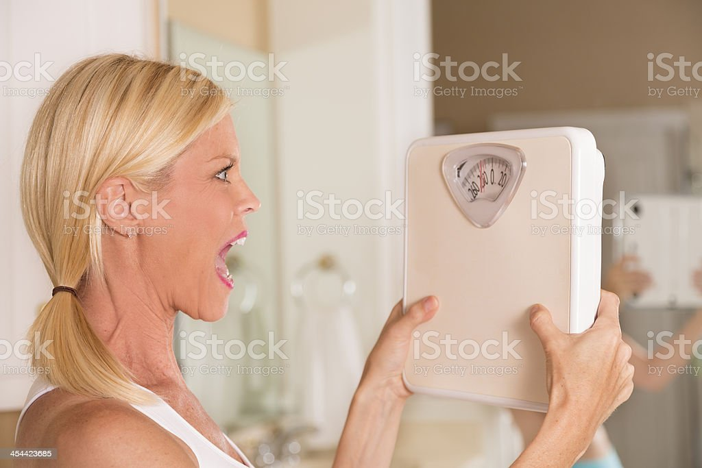 Healthy Lifestyle:  Weight conscious woman yelling at her scale. royalty-free stock photo