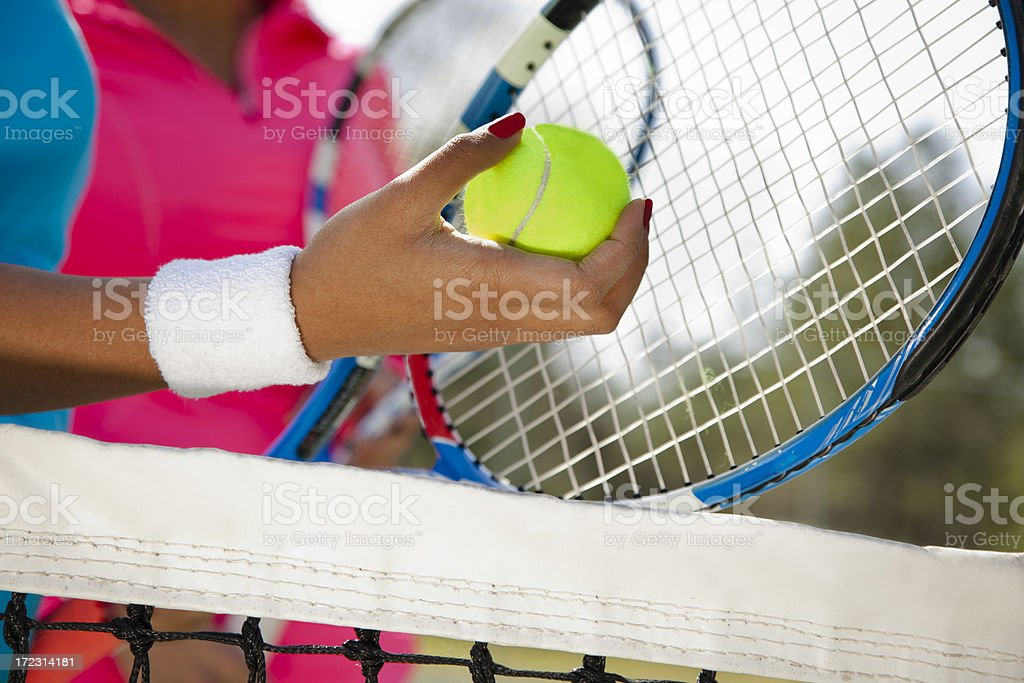 Healthy Lifestyle: Woman holds tennis ball standing next to teammate royalty-free stock photo