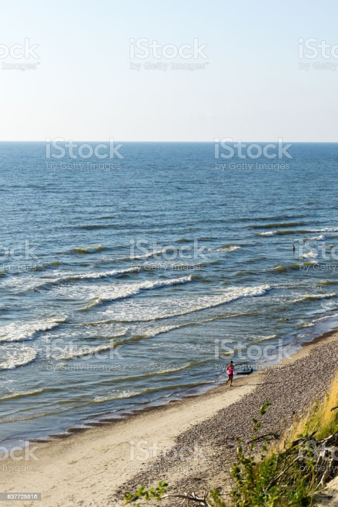 healthy lifestyle, woman running on the beach near sea in the evening with sunlight, perfect woman body stock photo