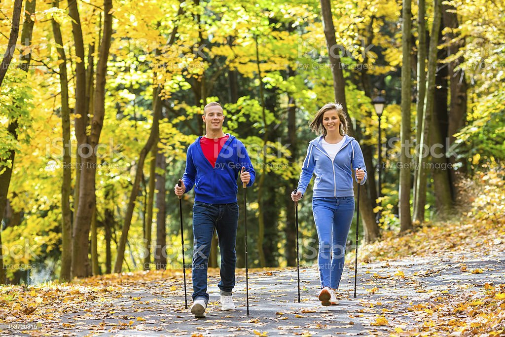 Healthy lifestyle - young people Nordic walking in park stock photo