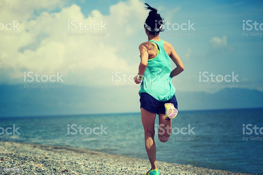 healthy lifestyle young woman runner running on seaside stock photo
