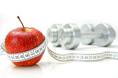 Healthy Living Concept - Apple with tape measure and dumbbells.