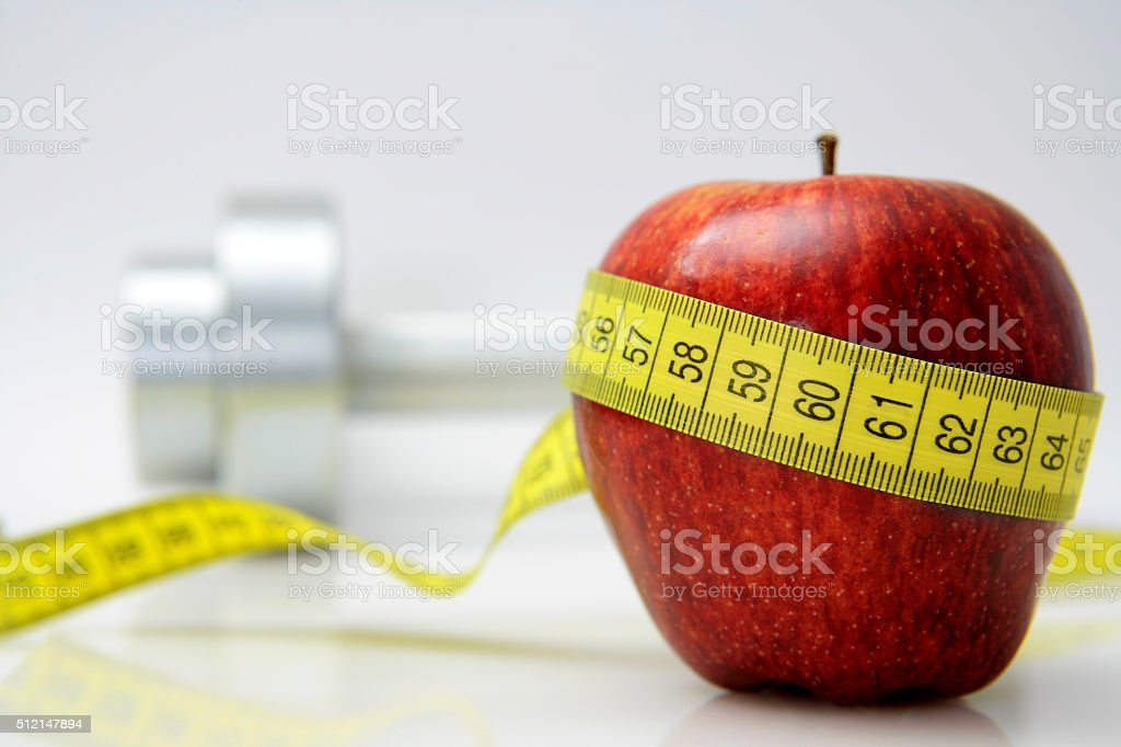 Healthy Living Concept - Apple with tape measure and dumbbells. stock photo