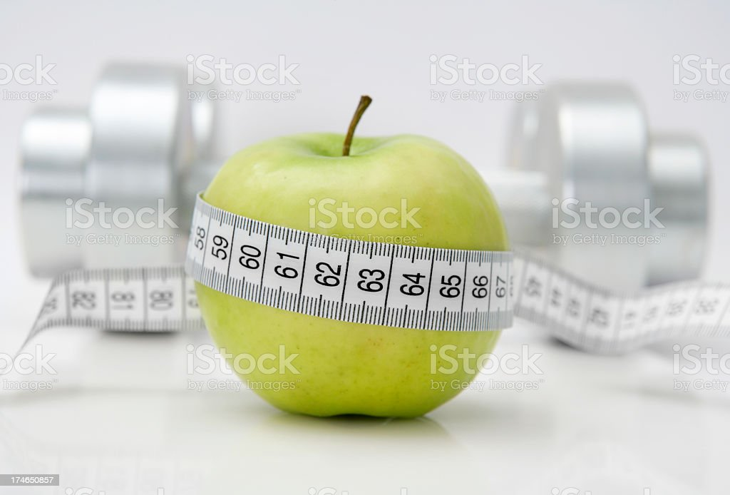 Healthy living exemplified by tape measure circling apple royalty-free stock photo