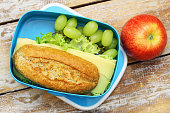 Healthy lunch box containing brown cheese roll, red apple, grapes