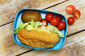 Healthy lunch box: whole grain cheese sandwich, kiwi, cherry tomatoes