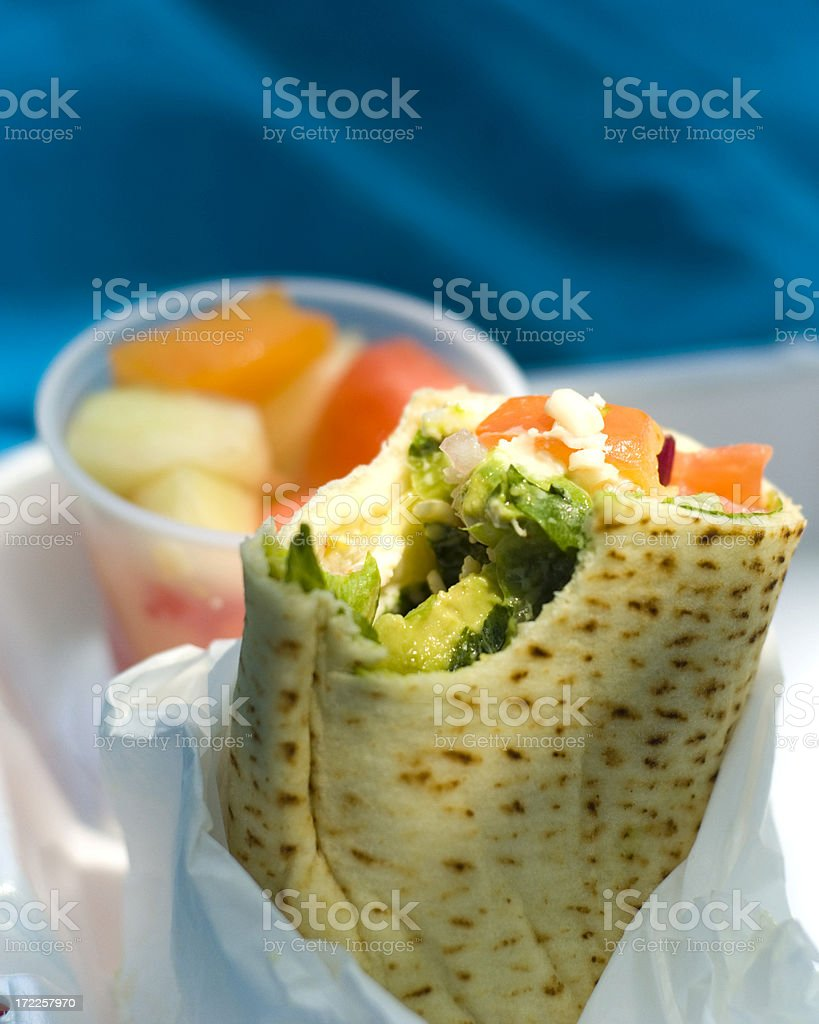 A healthy lunch consisting of a chicken wrap and fruit royalty-free stock photo