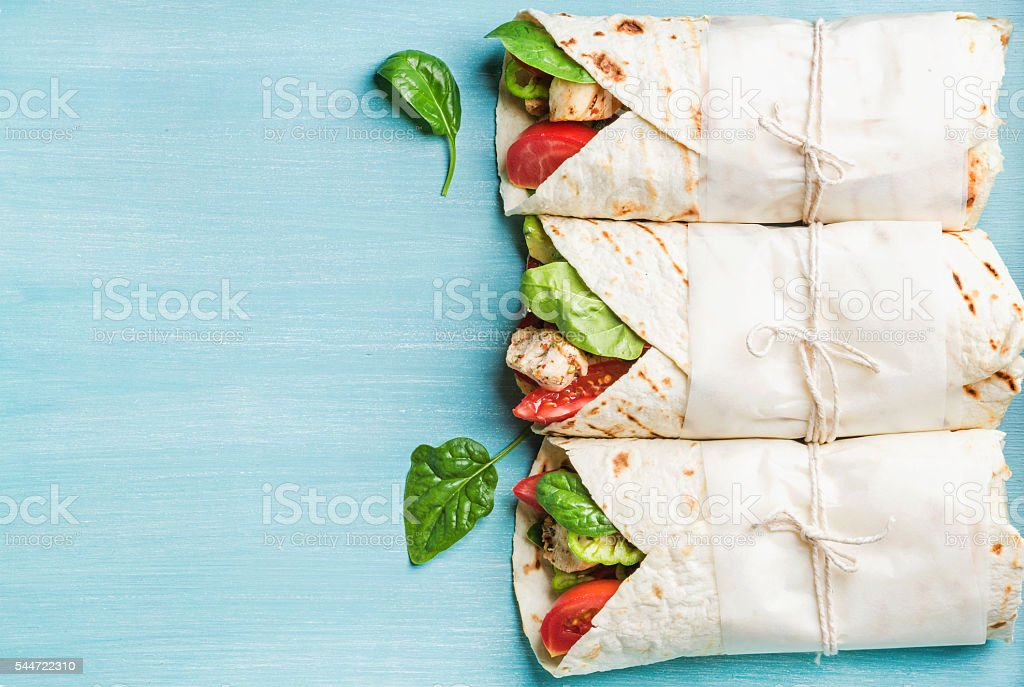 Healthy lunch snack. Three tortilla wraps with grilled chicken fillet stock photo