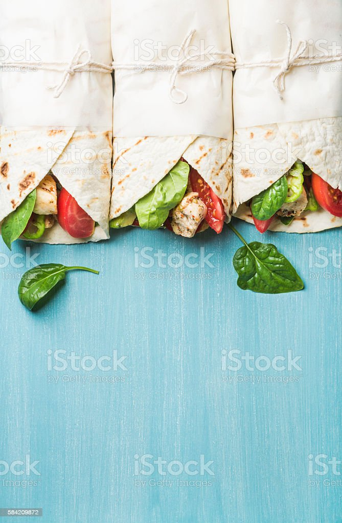 Healthy lunch snack. Tortilla wraps with grilled chicken fillet and stock photo