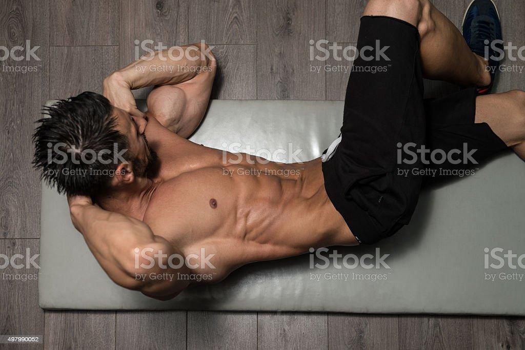 Healthy Man Doing Abdominal Excerise On Foor stock photo