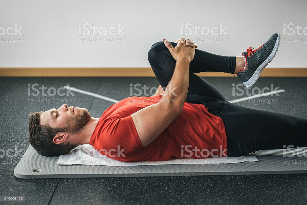 healthy man stretching leg before gym workout stock photo