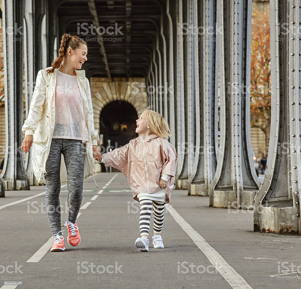 healthy mother and child on Pont de Bir-Hakeim bridge walking stock photo