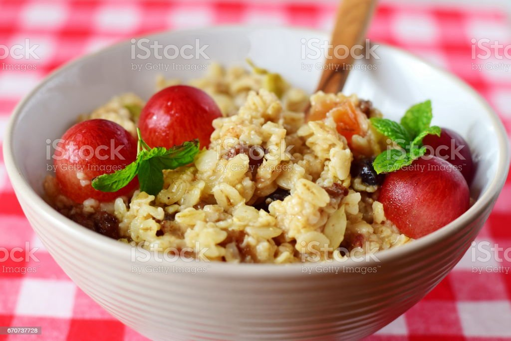Healthy Oatmeal recipes. Porridge in a ceramic bowl with grapes on a red background. stock photo