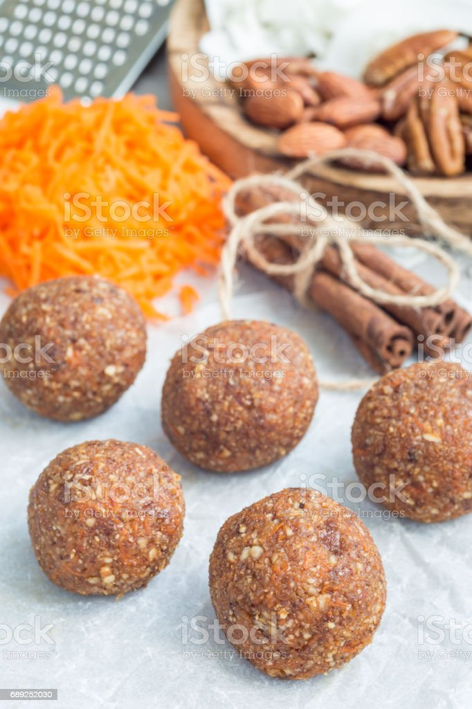 Healthy paleo energy balls with carrot, nuts, dates and coconut flakes, on parchment, vertical stock photo