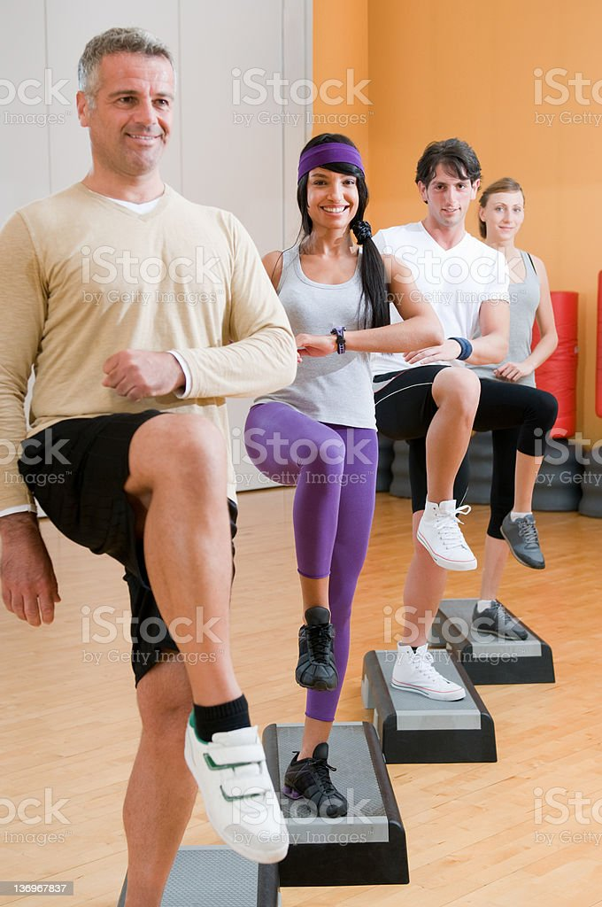 Healthy people doing exercises at gym royalty-free stock photo
