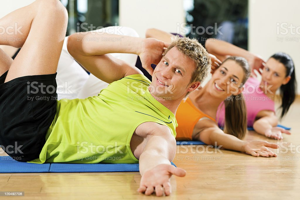 Healthy people doing synchronized side crunches at the gym royalty-free stock photo