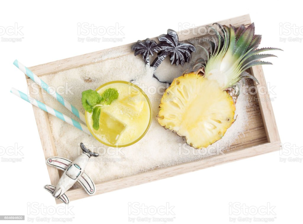 healthy pineapple drink with toys in sand on wooden tray stock photo