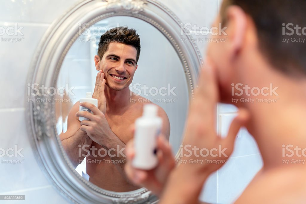 Healthy positive male treating sking with lotion stock photo