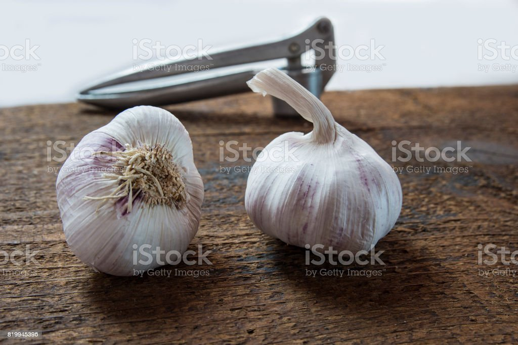 Healthy purple garlic on the wood with the chopper stock photo