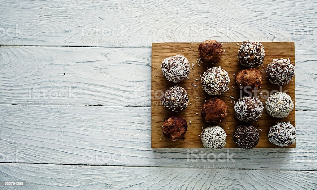 Healthy raw energy balls on a white wooden background stock photo