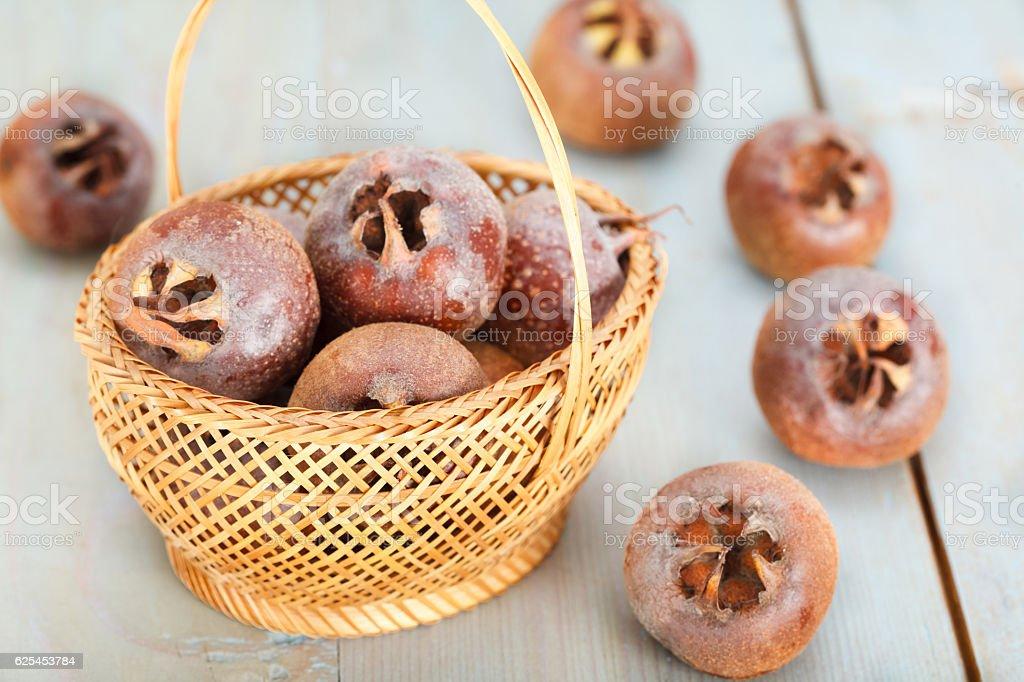 Healthy ripe Medlar fruit in basket stock photo