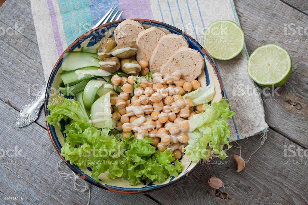 healthy salad in a bowl. olives, lime, chickpeas, paprika tofu, stock photo
