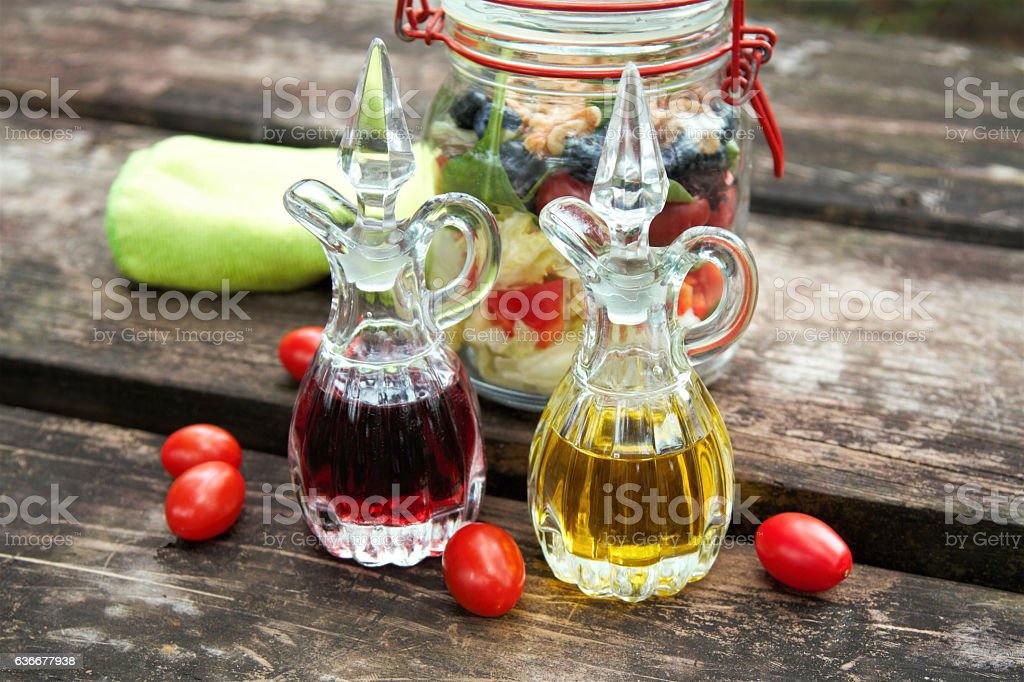 Healthy salad in a jar with cruets of dressing stock photo