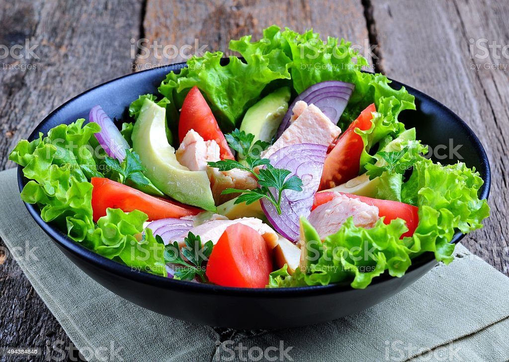 Healthy salad of avocado, tomatoes, canned tuna, onions and lettuce stock photo