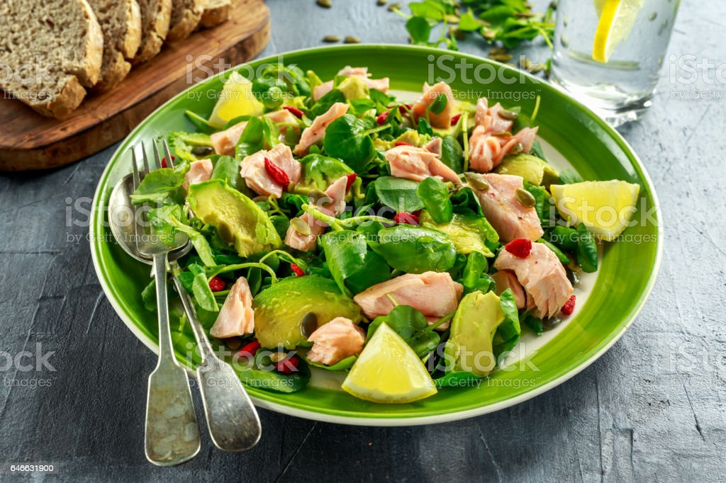 Healthy Salmon, Avocado salad with watercress and goji berries, pumpkin seed mix on green plate stock photo